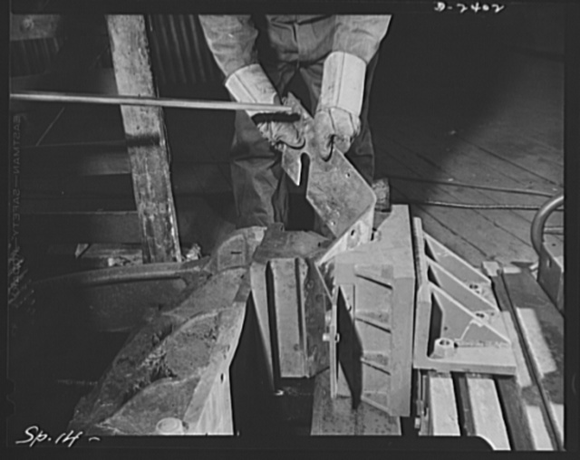 Conversion. Merry-go-round plant. These hands used to turn out merry-go-rounds to gladden the hearts of the nation's children. The carrousel plant in which they work is now engaged in producing war parts in subcontracts from army and navy contractors. Here the hands, which belong to Otto Andre, are bending crate hooks for the packing of airplane engines for export. The bulldozer was used in peacetime work, has since been converted to war work. Spillman Engineering Company, North Tonawanda, New York
