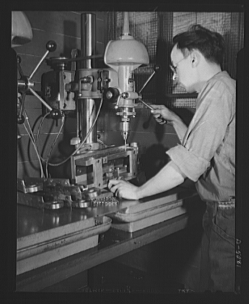 Conversion. Paper machinery to plane wing parts. A drill press operator bores holes in an airplane wing hinge in the plant of an Eastern paper machinery manufacturer. The hinge is clamped to the under side of a drill jig. The company also makes naval sights and other war essentials