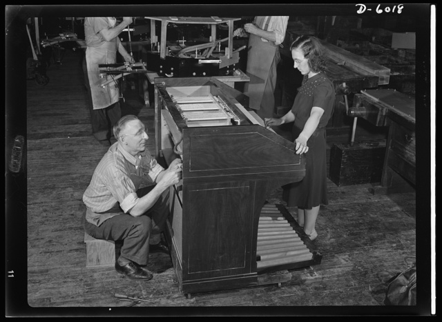 Conversion. Pianos to airplane motors. The lost chord won't be found till the war is over! One of the last electric organs to be made for the duration comes off the line in a Chicago factory now converted to war production. Note octagonal trainer-plane motor in background already undergoing assembly. Gulbransen Company