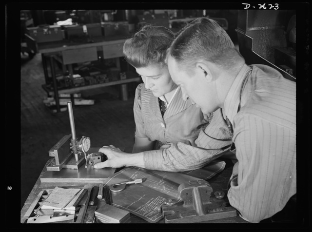 Conversion. Safety razor plant. Checking dimensions of completed V-block, shop supervisor George Cole explains testing processes to Edith Krause. Both these workers have graduated from razor blades to tool posts because of the company's subcontract for production of war tools