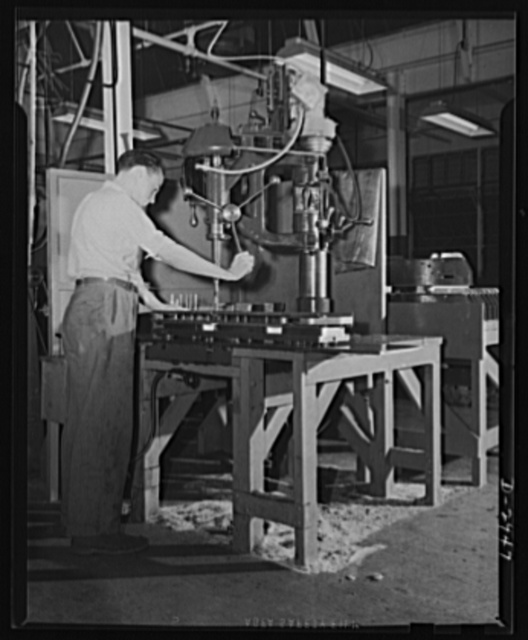 Conversion. Silverware plant. Undergoing conversion to production of bomb shackles from silver tableware, employees of an Eastern plant are helping America deal death to the Axis. Reaming operations on shackle frames are shown above. Air Corps regulations demand extremely fine tolerance. Oneida Ltd., Oneida, New York