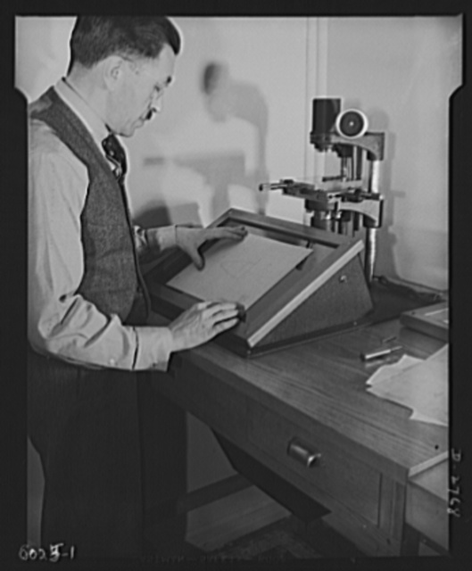 Conversion. Soft drink dispenser plant. The president of an Eastern manufacturing company now producing war essentials on prime and subcontracts, checks a contour gauge manufactured for Army arsenals. Gauges for measuring cartridges and other war materials must be accurate to the 2/10,000 of an inch to meet ordnance specifications. Bristol and Martin Company, New York, New York