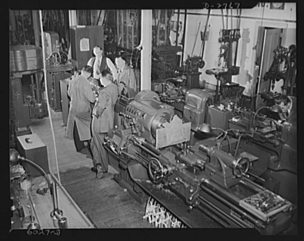 Conversion. Soft drink dispenser plant. These machines are working for Uncle Sam instead of manufacturing such civilian items as soft drink dispensers and game boards. Inspecting operation of a tool room lathe are officials of this company which is producing tools for cartridge manufacture, brass quadrants and other war essentials. Bristol and Martin Company, New York, New York