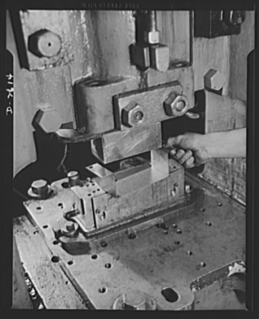 Conversion. Toy factory. Between the heavy punch and the die, a vital war product is being turned out by a press which once produced only metal toys and movie projectors. U-shaped object is part of radio filter box essential to the army. Keystone