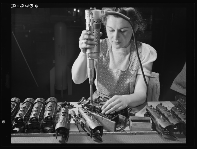 Conversion. Toy factory. From toy trains to parachute flare casings is the work history of Stephanie Cewe, whose skill with this electric screwdriver has been turned to the aid of Uncle Sam's war machine. Here she is shown at her former job--assembling locomotives for toy trains. Today she operates the same screwdriver in her assembly work on flare casing. A. C. Gilbert Company, New Haven, Connecticut