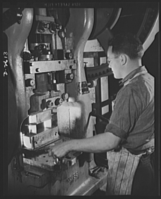 Conversion. Toy factory. Skillfully operating this massive press, a worker stamps out part of a filter box essential to the armed forces. Before conversion of this machine, metal toys were stamped out. The changeover consisted chiefly of new dies. Keystone