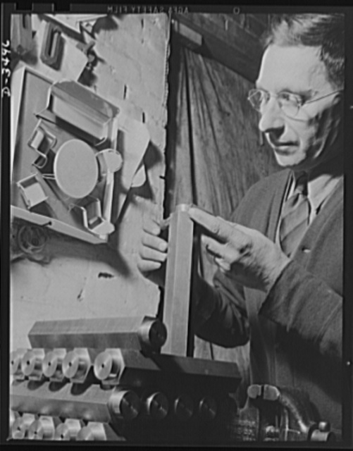 Conversion. Toy furniture to dies for incendiary bombs. Dies to destroy the Axis. The owner of this small Midwest factory inspects dies for making incendiary bombs. Note doll's furniture on the wall, the company's previous product. Complete conversion of all machines for this factory's production of war essentials is rapidly taking place. Sivon Machine Company, Painesville, Ohio