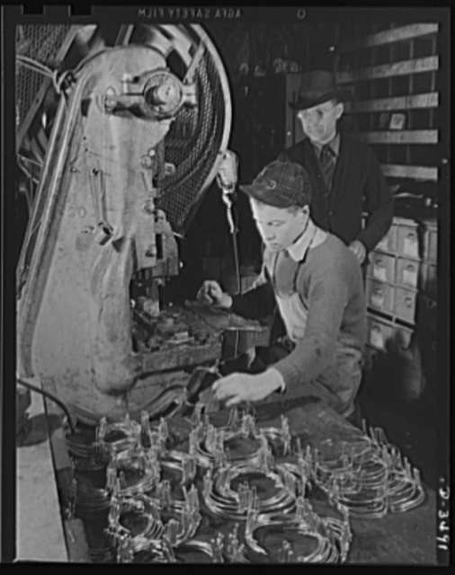 Conversion. Toy furniture to dies for incendiary bombs. This small Midwest machine shop used to manufacture doll's furniture and fly swatters before Pearl Harbor. Subcontracts on defense orders now occupy all machines as rapidly as the old stock can be assembled. Here two high school boys complete machine work on metal legs for the furniture. Sivon Machine Company, Painesville, Ohio