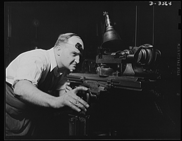 "Conversion. Watch cases to war production. Sighting one of the ""guns"" of production. A diemaker in a converted Kentucky watch case factory sets his machine for the production of fine parts for carbines, machine guns and military radios. Wadsworth Watch Company, Louisville, Kentucky"