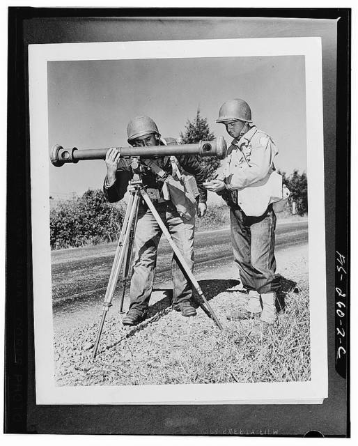 Corporal Hanry Manoni and Sergeant Joseph Loftis sight through a rangefinder in the process of aiming big guns of their artillery battery during Second Army maneuvers in Tennessee
