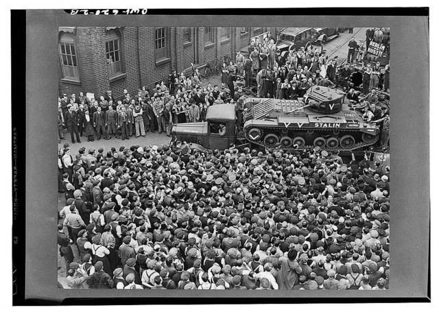 """Crowds of people and a guard of honor of tanks, meeting M. Maisky, Soviet ambassador, and members of the Rusian military mission when they arrived at a tank factory somewhere in Great Britain(?), where the week's tank production is for Russia, showing the """"Stalin"""" tank, which had just been christened by Madame Maisky"""