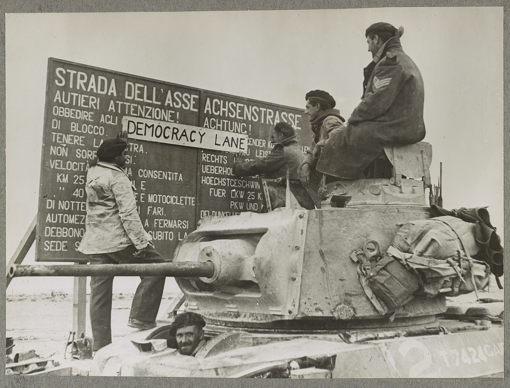 "Cyrenaica reconquered: Later pictures from the battlefront The Axis highway (""Strada Dell'Asse"") rechristened ""Democracy Lane"" - members of a British tank crew affixing the new name over the original Italo-German notice-board somewhere in Cyrenaica. The crew had been in the thick of the fighting."