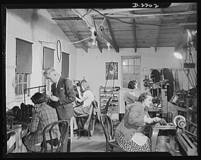 Dante Electric Company, Bantam, Connecticut. One of the many small shops throughout the nation making articles of the War Production Program. Here in the women's department of the Dante Electric Company, three workers of the Dante family help in the production of electrical parts for submarines. Mr. Dante just made a slight adjustment on the mechanical screw driver operated by Mrs. Hazel Wheeler. In the center, Mr. Artie Shaw is working on a similar machine. Bertha Kreig, of nearby Harwinton, is working at the right rear