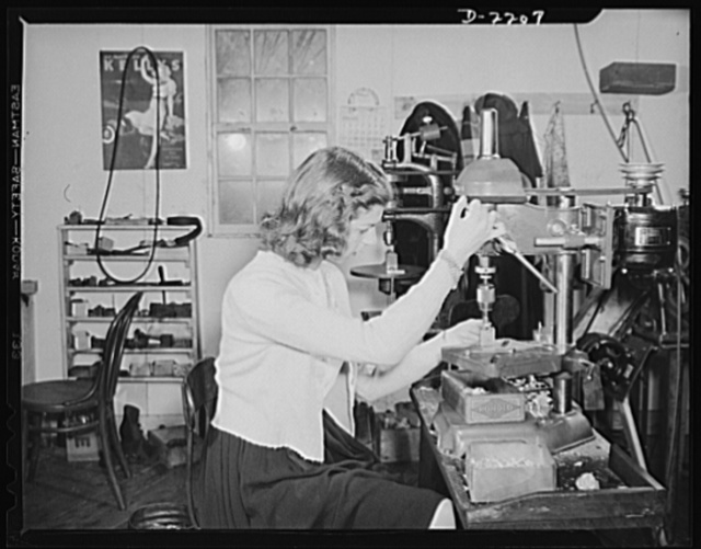 """Dante Electric Company, Bantam, Connecticut. The shop is busy, so Anna, oldest of the five Dante girls lends a hand with a drill press. Anna operates the Bantam Beauty Salon, but because she has difficulty with hot water during the winter, she closes the shop from early January through March. Her """"boyfriend"""" (Anna says they are not engaged) works regularly at the American Brass Company in Torrington. If he puts in an eight-hour day there, he works for another four hours at the Dante Electric. Often now, however, he puts in a twelve-hour day in Torrington, and on those days does not work for Dante"""