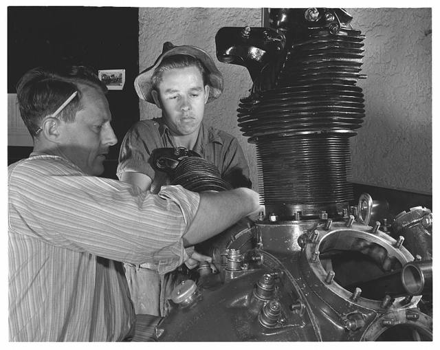 De Land pool. Aircraft construction class. Instructor Gil Angell shows Ernest Williams, high school student, how to install a cylinder on an aircraft engine in the Daytona Beach, Florida Vocational School that is turning out hundreds of workers for Florida's war production program