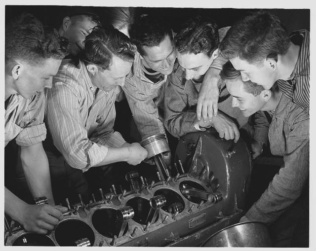 De Land pool. Aircraft construction class. These carefree high school students are learning the serious business of war production in a Daytona Beach, Florida vocational school located in a revamped nightclub. Instructor Gil Angell (with piston in his hand) is showing the group how to assemble an airplane engine. Left to right are Wilson, Flippo, Angell, Dewey Stewart, nineteen; Ken Kirkpatrick, eighteen; Bill Jackson and Ned Brown, eighteen. Jobs already are waiting for most of them when they finish their courses