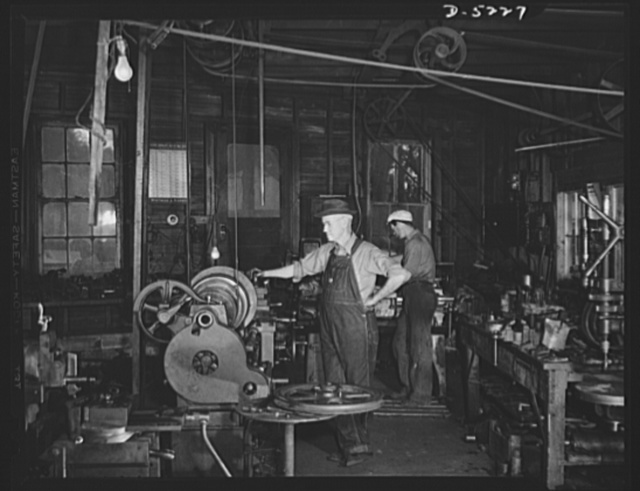 De Land pool. Bits and parts. Casey's machine shop in De Land, Florida doesn't have fluorescent lighting or air conditioning, but it does have the close tolerance machinery needed to make war weapons. Casey and his one-man crew are shown here as they turn out repair racks for airplanes