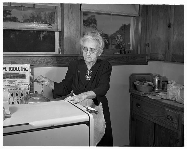 De Land pool. La Roe shop. Seventy-five-year-old Mrs. Katie La Roe, great-grandmother of the family, does the cooking for the La Roe production group at Eustis, Florida to give other members of the family more time for war work in their garage machine shop. The La Roe family forms an important unit in the De Land, Florida industrial pool.