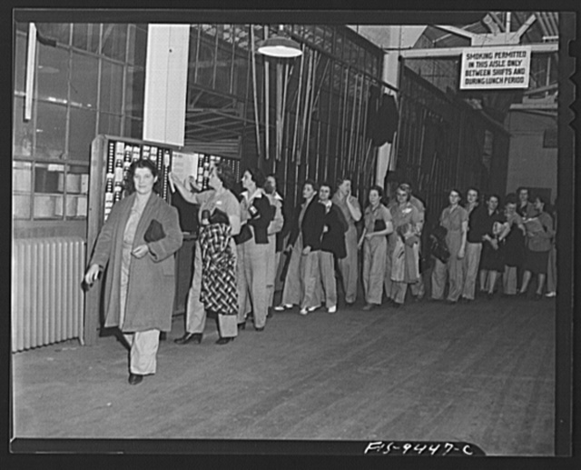 De Soto bomber plant, Detroit, Michigan. Women war workers wearing slacks check out at end of a shift