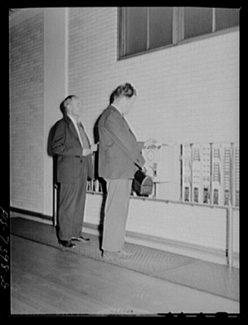Dearborn, Michigan. Karl Westerberg and his son Eric punching the time clock at the entrance to the Ford Motor Company where Eric is an expert tool and die maker and his father is foreman of the rough stock division of the Johansson gauge division
