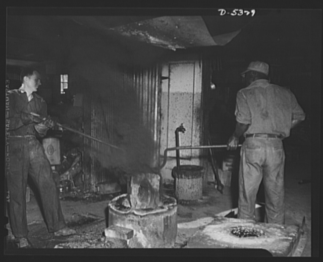 DeLand pool. Improvised foundry, Daytona Beach. Important workers in the DeLand, Florida, industrial pool. R.G. Campbell, foundry foreman, and his Negro helper, Arthur Brown, who used to work in an orange grove, draw the homemade crucible, filled with molten metal, out of the tiny blast furnace improvised from old equipment by J.L. Clayton, city fireman at Daytona Beach