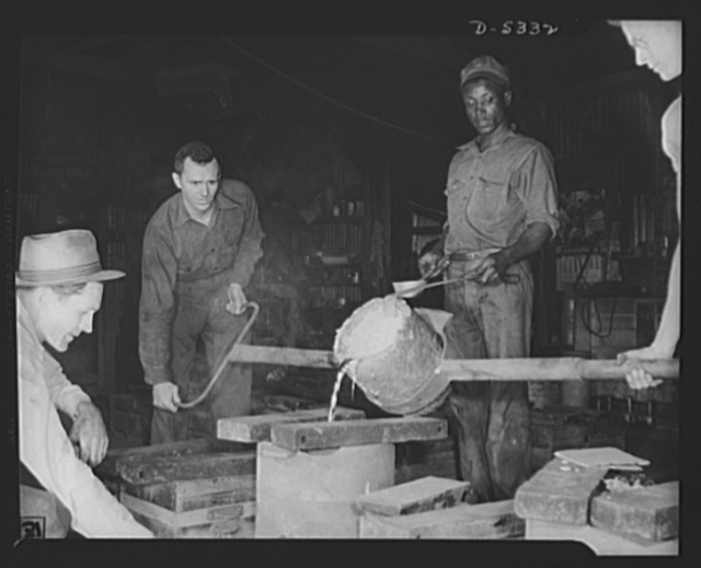 DeLand pool. Improvised foundry, Daytona Beach. Molten aluminum spills like quicksilver from this homemade bucket-sized ladle and pours white-hot into a mold to cast experimental parts for bombers in Clayton's foundry at Daytona Beach, Florida. Foundry foreman R.G. Campbell watches the color of the pour from the left. J.L. Clayton, city fireman, who built the foundry as a hobby, is pouring with the aid of his Negro helper