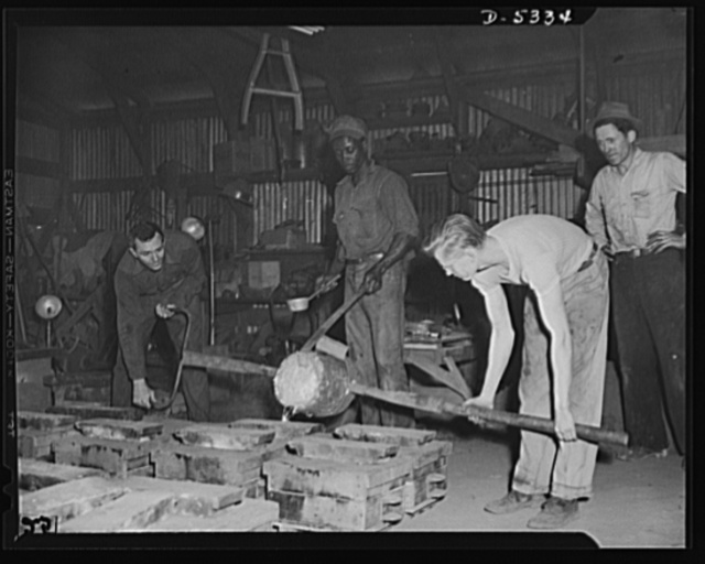 """DeLand pool. Improvised foundry, Daytona Beach. The """"pour"""" in a foundry at Daytona Beach, Florida, designed by city fireman J.L. Clayton. R.G. Campbell, foundry foreman, left, is controlling the homemade ladle. Arthur Brown, Negro helper from an orange grove, guides the crucible, while Lewis Pillitz, formerly an electrician, helps on his end. The molds are for air raid sirens of Clayton's own design"""
