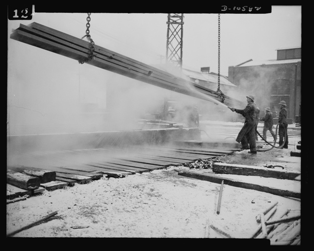 "Denver, Colorado. Workers giving ship steel a thorough rinsing after it has been ""pickled"" in the highest steel ""pickling"" vat in the world. The ""pickling"" operation, giving steel a sulphuric bath to remove mill scale, is a common sight at Seaboard Shipyards, and is something unique at the mile-high Denver fabricating plant and an illustration of American industrial ingenuity"