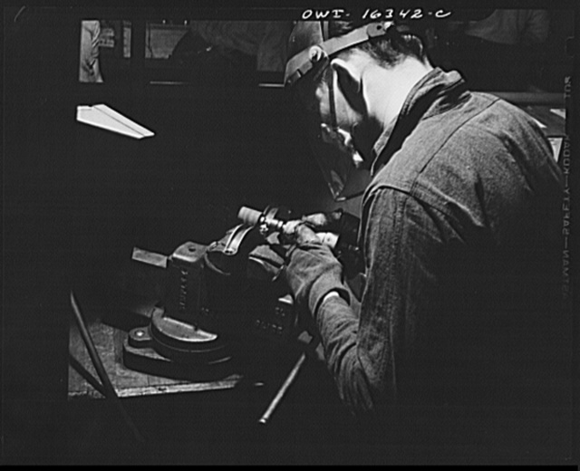 Detroit, Michigan. A box for suggestions from workers installed in the Cadillac motor ar division of General Motors Corporation (?) with a jig holding two parts in a vise. A worker suggested the design for a jig to hold six of these parts at once, and so cut down handling time