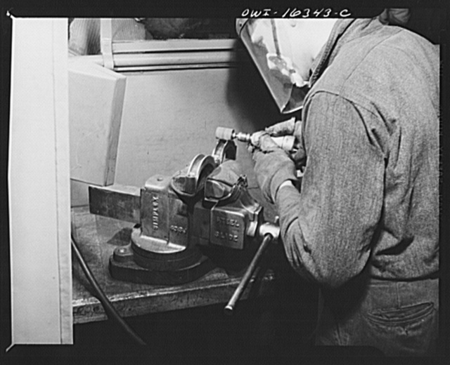 Detroit, Michigan. An operation at the Cadillac motor car division of General Motors Corporation (?) with a jig holding two parts in a vise. A worker suggested the design for a jig to hold six of these parts at once, and so cut down handling time