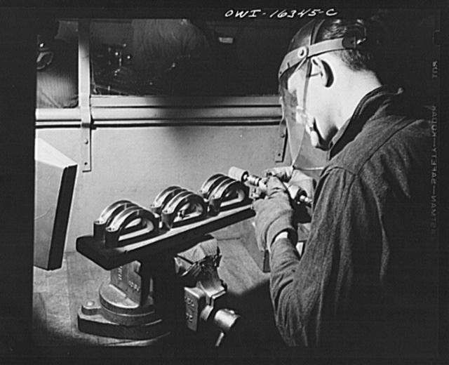 Detroit, Michigan. An operation at the Cadillac motor car division of General Motors Corporation (?) showing a jig for holding six parts instead of two, as suggested by a worker so as to reduce handling time
