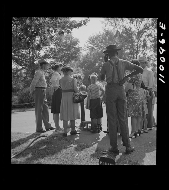 Detroit, Michigan. Group waiting to drink water out of a public fountain in the zoological park