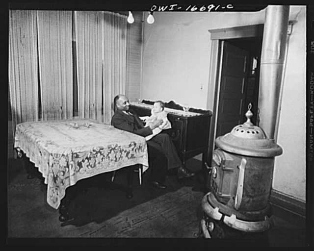 Detroit, Michigan. Negro father playing with baby daughter. Old style burner in the foreground. These are conditions under which families originally lived before moving to the Sojourner Truth housing project