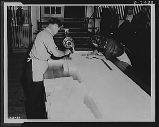 Discarded stockings go to war. Layers of silk cloth processed from discarded silk stockings are cut to specifications with a power knife at a government arsenal where the cloth is made into powder bags