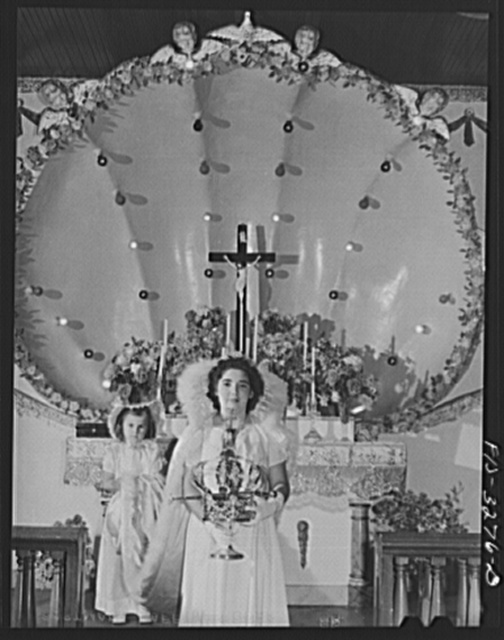 Dorothy Bettencourt, Queen of the Holy Ghost Festival of the Portuguese-Americans at Novato, California, in front of the altar in the I.D.E.S.I. hall. She holds the crown which she will wear after special mass is said