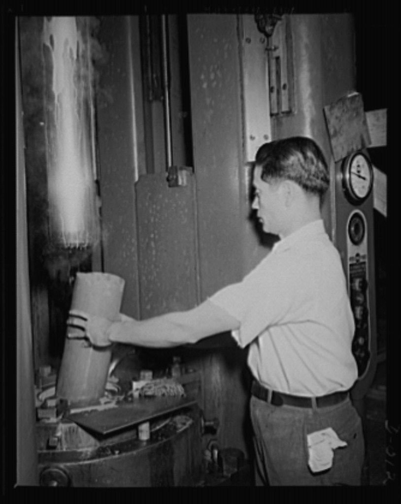 Drawing of a cartridge case. Skilled worker drawing a five-inch cartridge case for the big anti-aircraft guns. The yard in which the work is performed is one of eleven Navy yard arsenals which are working at top speed to furnish ammunition needed for our two-ocean Navy