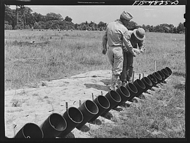 Edgewood Arsenal, Maryland. Gas demonstration. Connecting the wiring on a battery of twenty five Livens projectors for the firing of shells containing gas