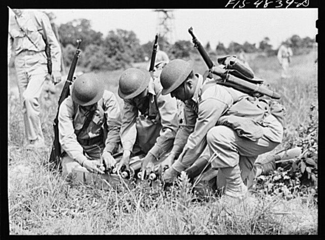 Edgewood Arsenal, Maryland. Gas demonstration. Mortar crew removing caps from shells which they are about to fire