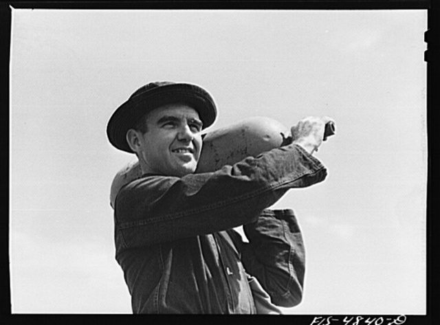 Edgewood Arsenal, Maryland. Gas demonstration. Soldier with one of the gas shells for Livens projectors