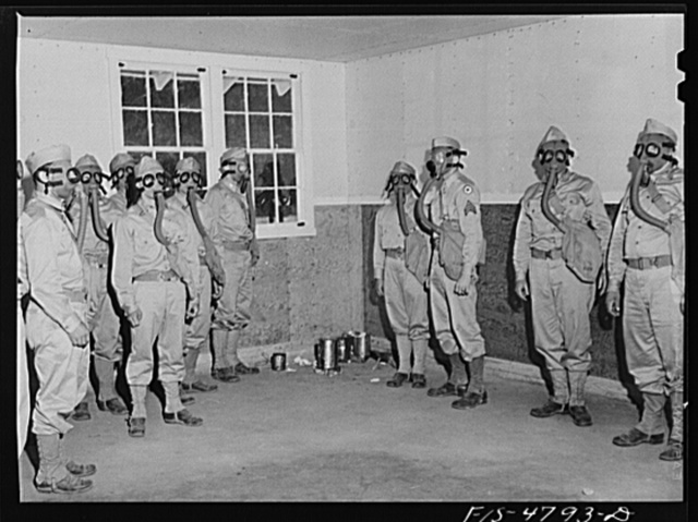 Edgewood Arsenal, Maryland. Gas demonstration. Soldiers in the gas chamber filled with tear gas which emanates from cans on the floor in the corner