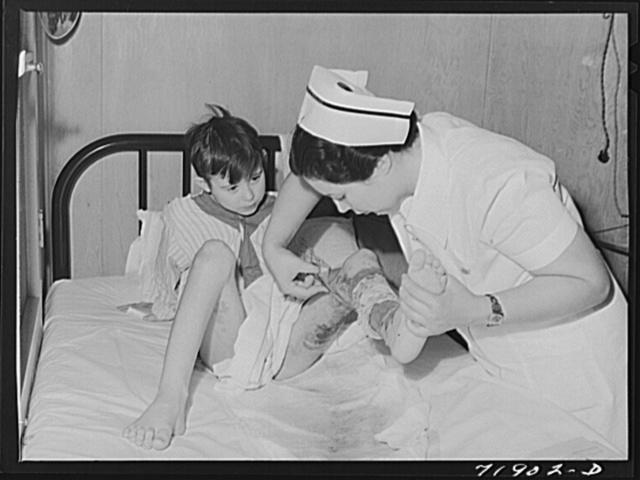 Eleven Mile Corner, Arizona. Cairns General Hospital, FSA (Farm Security Administration) farm workers' community. Nurse removing a patient's bandage
