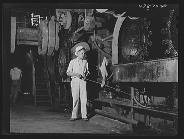 Ensenada, Puerto Rico. Workman at one of the giant grinding machines in the South Puerto Rico Sugar Company