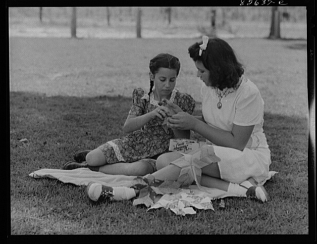 Escambia Farms, Florida. Elena McLelland giving her sister, Kitty, a sewing lesson on the family lawn on a Sunday