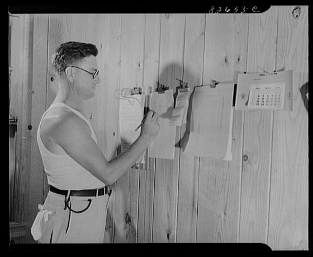 Escambia Farms, Florida. Mr. McLelland keeping his accounts straight