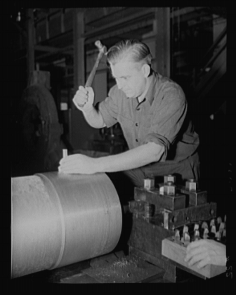 Every knock a boost. A little careful hammer work pushes a big gun along toward completion in an eastern arsenal. The man shown is stamping the location line on a medium-caliber gun