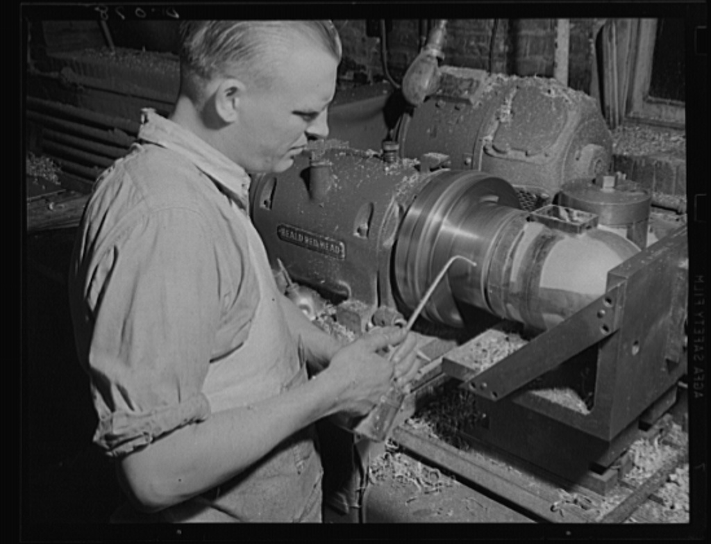 Expert machinist on armaments. Boring and facing a setter fuze in one operation at a large eastern arsenal working full speed for total war