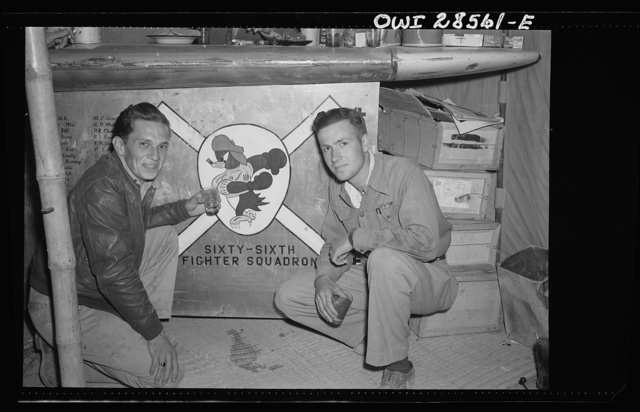 Exterminators lived up to their name. Lieutenant John Stefanik (left) of Chicopee, Massachusetts, and Lieutenant Charles Leaf, of South Orange, New Jersey, display the insignia of their Sixty-Sixth Squadron, one of the units of the Fifty-Seventh Fighter Group, United States Air Force. When the Fifty-Seventh knocked seventy-four Axis planes out of the skies in one air battle, the Exterminators accounted for more that twenty-five
