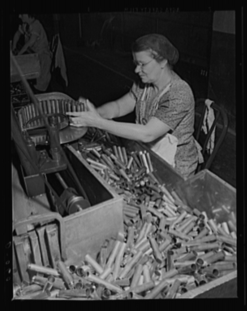 Feeding the modern machine. Skilled women as well as men are working on the country's armaments. These 50-caliber cartridge cases for guns are being tapered at a large eastern arsenal