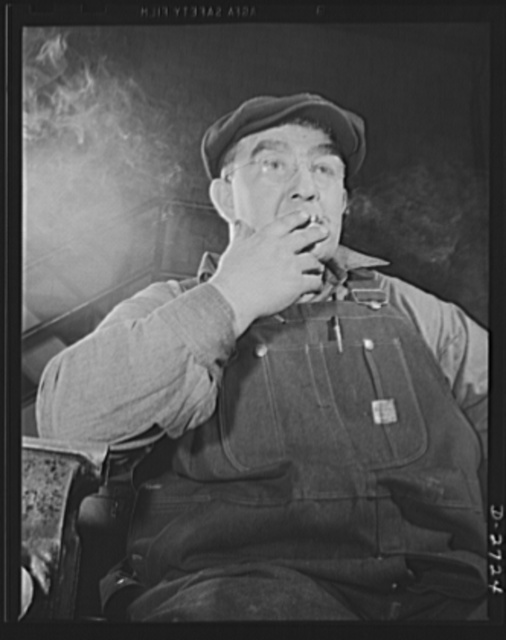 Fiberglass manufacture, Owens-Corning, Toledo, Ohio. A machine maintenance man in a plant of the Owens-Corning Fiberglass Corporation enjoys a smoke as he goes off the shift