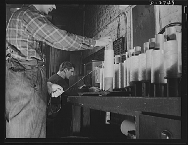 Fiberglass manufacture, Owens-Corning, Toledo, Ohio. A quality control inspector in a plant of the Owens-Corning Fiberglass Corporation checks the weight of staple glass fiber to insure conformity with rigid specifications